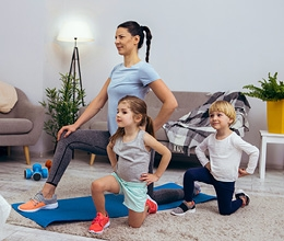 Mom with two kids doing yoga in living room