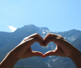 Heart hands capturing mountain views