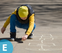 Kid drawing hotscotch board on ground with chalk