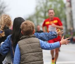 Kids with hands out for high-fives to cheer on run racers!