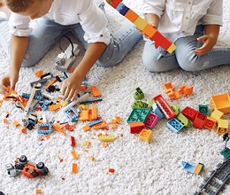 Kids playing with LEGOS on white carpet
